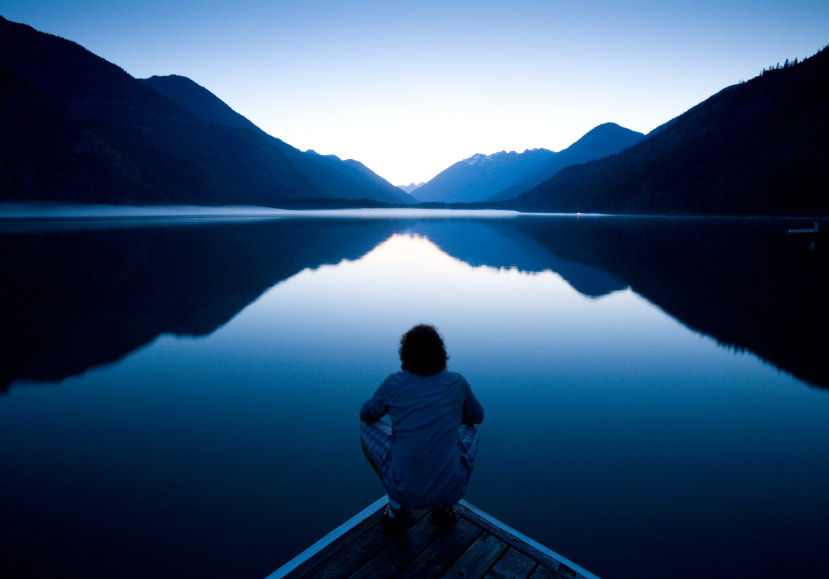Man reflecting in front of water